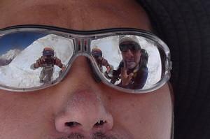 平賀カメラマンのサングラスを鏡に日焼け止めを塗る