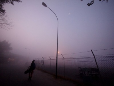 朝靄の中、ギターを担ぎ飛行場へ向かう亮さん
