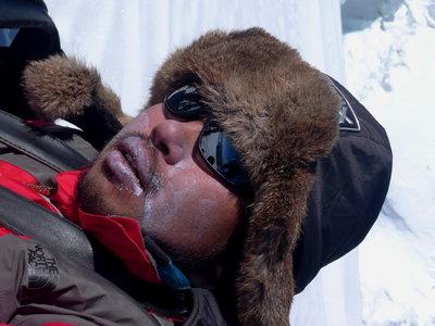 雪の上で横になって休む平賀カメラマン